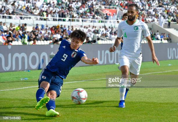 Takumi Minamino of Japan shoots while under pressure from Abdullah Otayf of Saudi Arabia during the AFC Asian Cup round of 16 match between Japan and...
