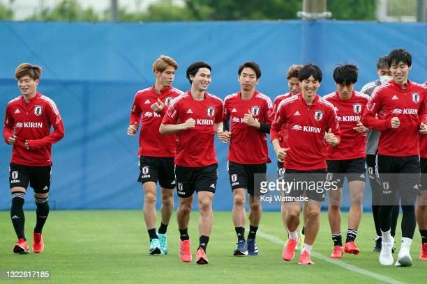 Takumi Minamino of Japan speaks on with team mate during the Japan training session on June 08, 2021 in Suita, Osaka, Japan.