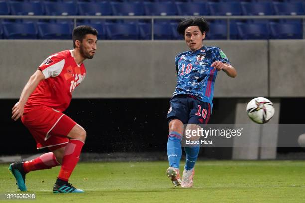 Takumi Minamino of Japan takes on Akhtam Nazarov of Tajikistan during the FIFA World Cup Asian Qualifier 2nd round Group F match between Japan and...
