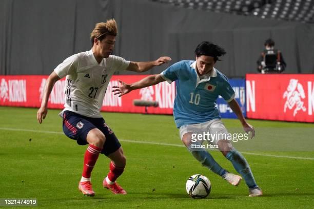 Takumi Minamino of Japan takes on Daiki Hashioka of Japan U-24 during the friendly match between Japan and Japan U-24 at the Sapporo Dome on June 3,...