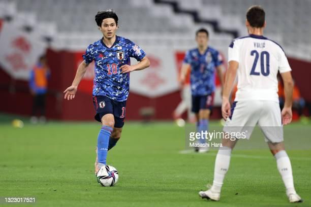 Takumi Minamino of Japan takes on Milos Vulic of Serbia during the international friendly match between Japan and Serbia at Noevir Stadium Kobe on...
