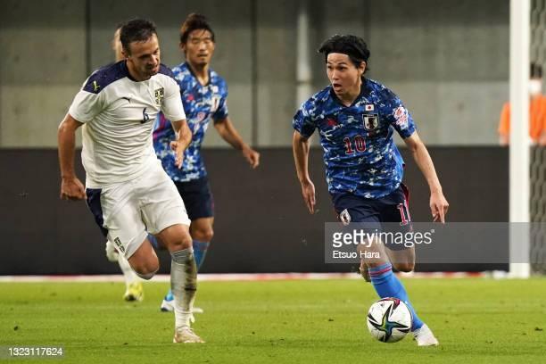 Takumi Minamino of Japan takes on Nemanja Maksimovic of Serbia during the international friendly match between Japan and Serbia at Noevir Stadium...