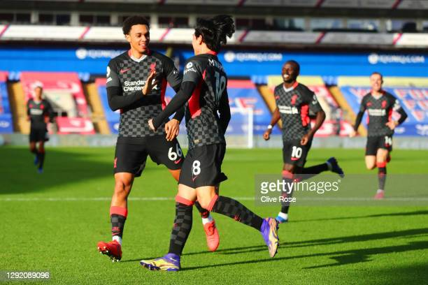 Takumi Minamino of Liverpool celebrates with teammate Trent Alexander-Arnold after scoring their sides first goal during the Premier League match...