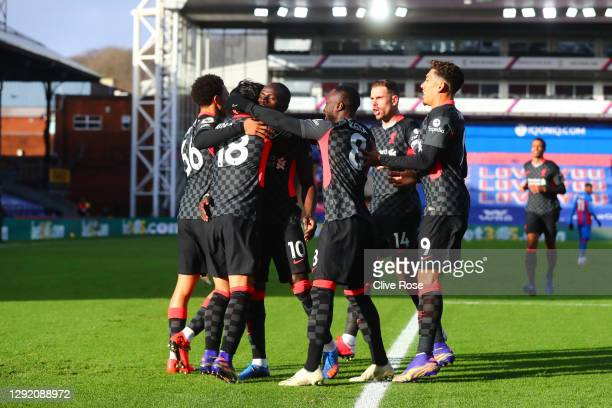 Takumi Minamino of Liverpool celebrates with teammates Trent Alexander-Arnold, Sadio Mane and Naby Keita after scoring their sides first goal during...