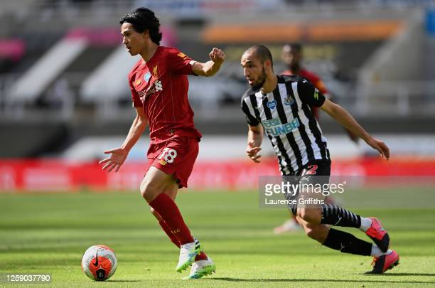 Takumi Minamino of Liverpool turns away from Nabil Bentaleb of Newcastle United during the Premier League match between Newcastle United and...