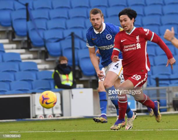 Takumi Minamino of Liverpool with Brighton & Hove Albion's Adam Webster during the Premier League match between Brighton & Hove Albion and Liverpool...