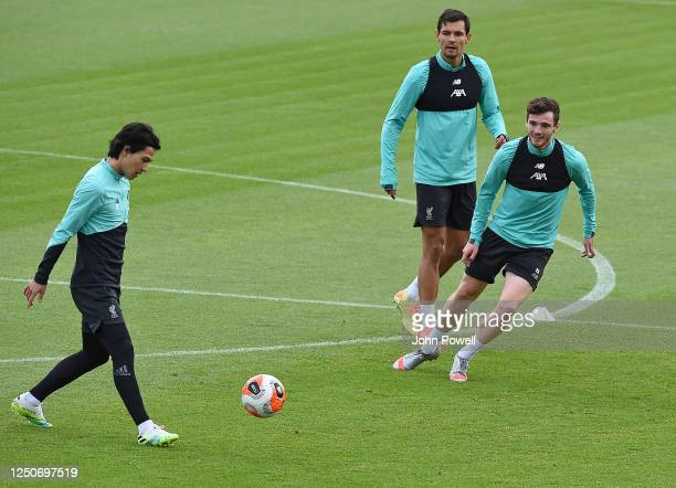 Takumi Minamino of Liverpool with Dejan Lovren of Liverpool and Andy Robertson of Liverpool during a training session at Melwood Training Ground on...