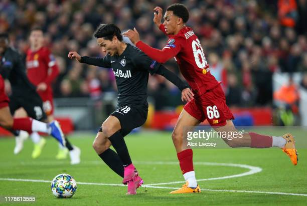 Takumi Minamino of Red Bull Salzburg and Trent AlexanderArnold of Liverpool clash during the UEFA Champions League group E match between Liverpool FC...