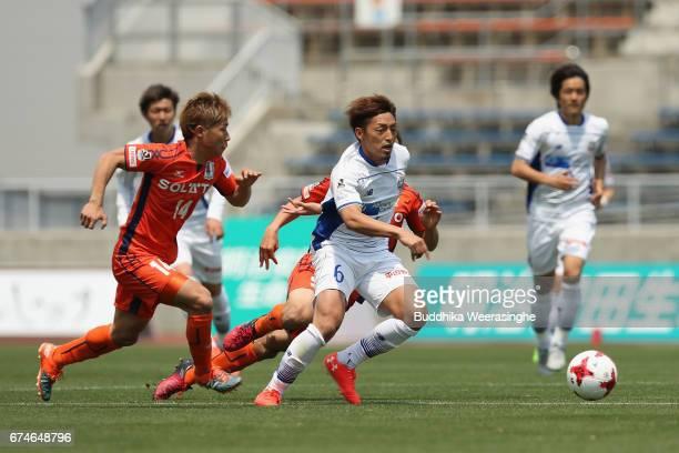 Takumi Yamada of Montedio Yamagata and Kosuke Shirai of Ehime FC compete for the ball during the JLeague J2 match between Ehime FC and Montedio...