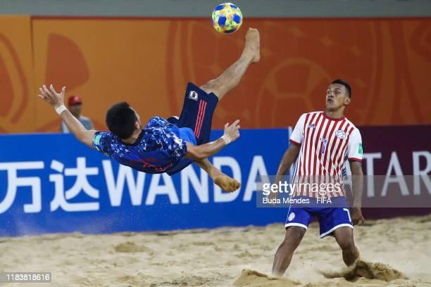Takuya Akaguma of Japan plays an overhead kick against Edgar Barreto of Paraguay during the FIFA Beach Soccer World Cup Paraguay 2019 group A match...