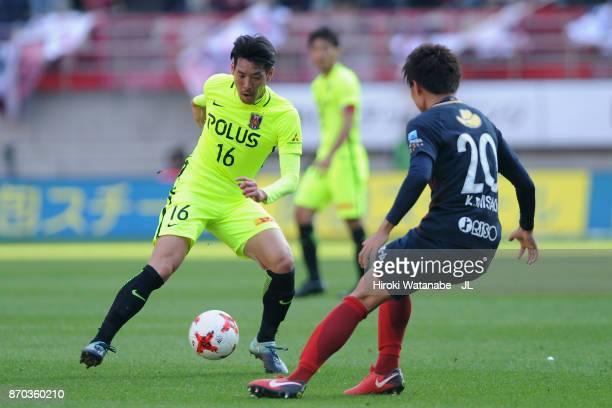 Takuya Aoki of Urawa Red Diamonds takes on Kento Misao of Kashima Antlers during the J.League J1 match between Kashima Antlers and Urawa Red Diamonds...