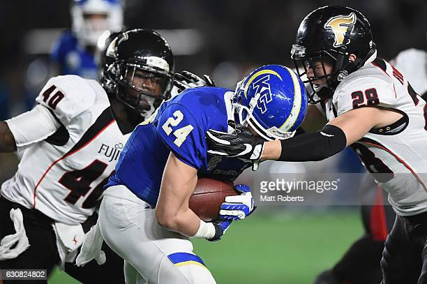 Takuya Ikenaga of the Fighters is tackled by Yuki Ishii of the Frontiers during the Rice Bowl match between Fujitsu Frontiers and Kwansei Gakuin...