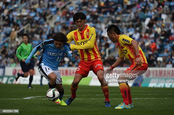 Takuya Matsuura of Jubilo Iwata dribbles the ball while Toru Miyamoto and Hiroyuki Nishijima of Giravanz Kitakyushu challenge during the JLeague...