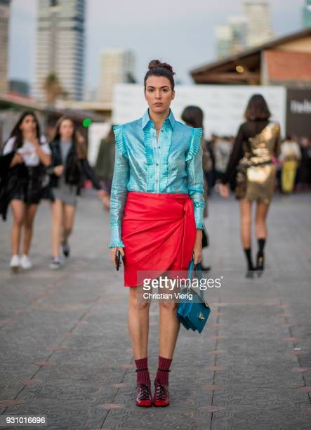 Tal Albalansi wearing red skirt, blue blouse, bag is seen during Tel Aviv Fashion Week on March 12, 2018 in Tel Aviv, Israel.
