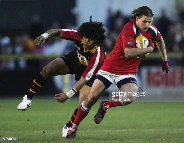 Tal Selley of the Scarlets charges upfield as Sione Tuipulotu of the Dragons misses a tackle during the Celtic Cup Quarter Final match between...
