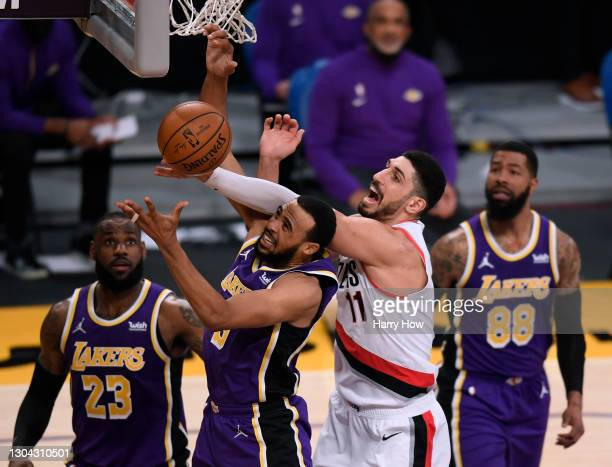 Talen Horton-Tucker of the Los Angeles Lakers gets a rebound in front of Enes Kanter of the Portland Trail Blazers LeBron James and Markieff Morris...