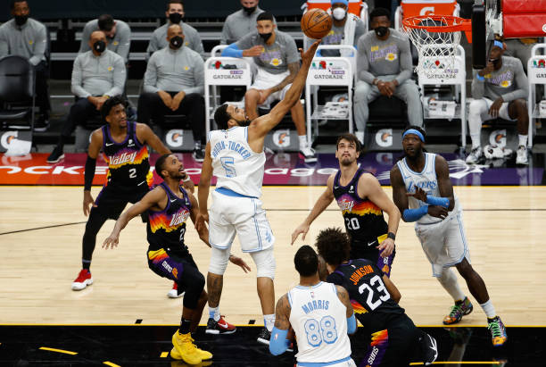 Talen Horton-Tucker of the Los Angeles Lakers lays up a shot over Dario Saric and Cameron Johnson of the Phoenix Suns during the first half of the...