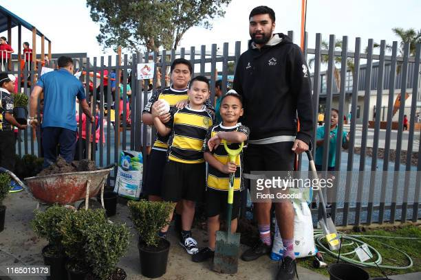 Taleni Seu of Waikato helps students of Koru School in Mangere plant shrubs during the Mitre 10 Cup Launch on July 30, 2019 in Auckland, New Zealand.