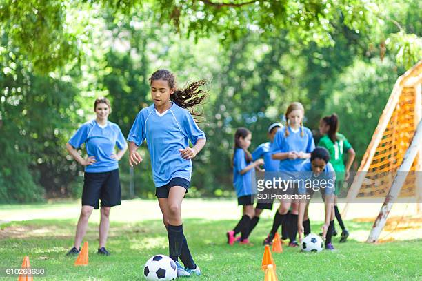 Talented soccer player kicks ball around practice cones