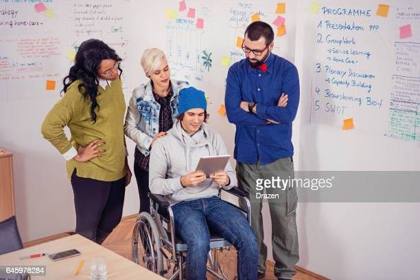 Talented young adults working together with disabled person in office
