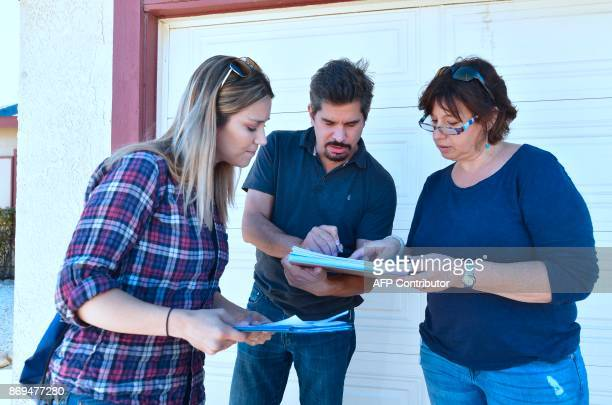 Talia Osteen Ari Posner and Becky Edwards look over adresses on their paperwork while participating in a morning canvassing of a residential...