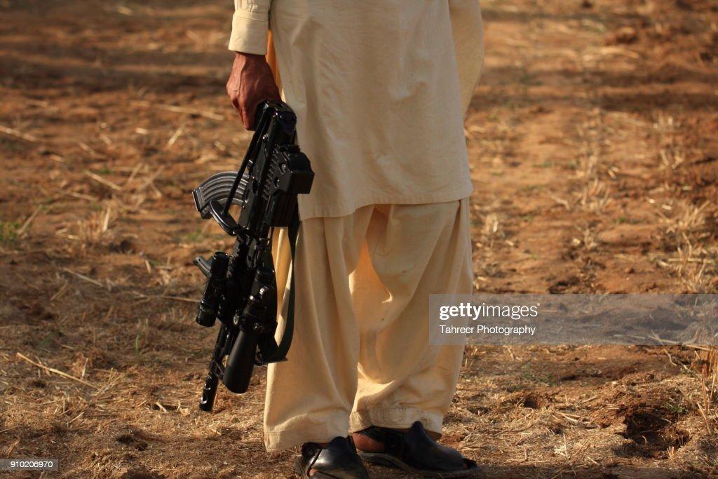 Taliban carrying a gun : Stock Photo