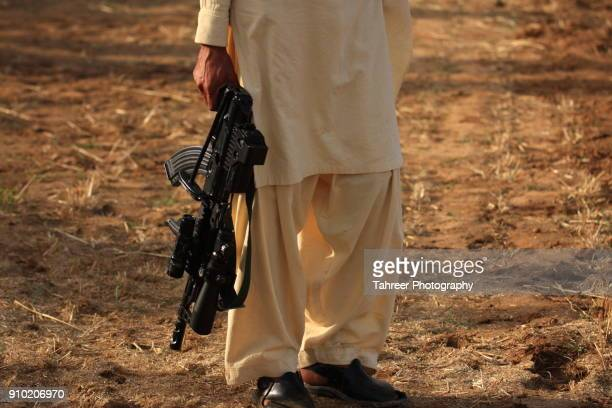 taliban carrying a gun - terrorism stock pictures, royalty-free photos & images