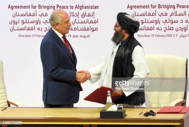 Taliban co-founder Mullah Abdul Ghani Baradar and U.S. Special Representative for Afghanistan Reconciliation Zalmay Khalilzad shake hands as they...