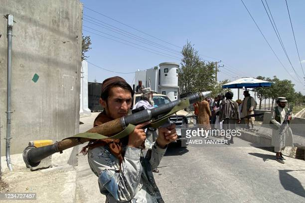 Taliban fighter holds RPG rocket propelled as he stands guard with others at an entrance gate outside the Interior Ministry in Kabul on August 17,...