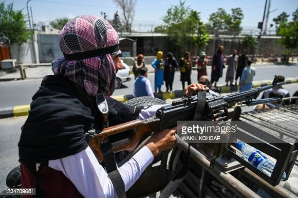 Taliban fighter mans a machinegun on top of a vehicle as they patrol along a street in Kabul on August 16 after a stunningly swift end to...