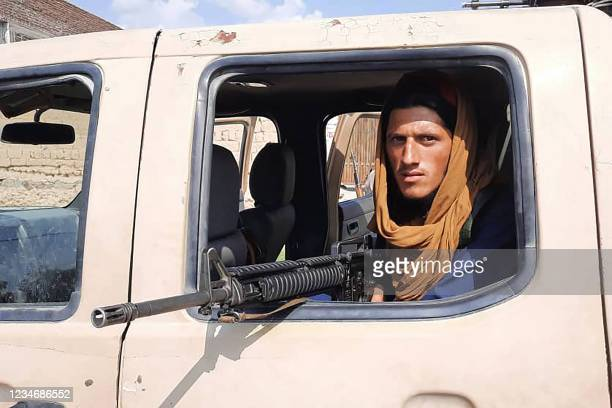 Taliban fighter sits inside an Afghan National Army vehicle along the roadside in Laghman province on August 15, 2021.