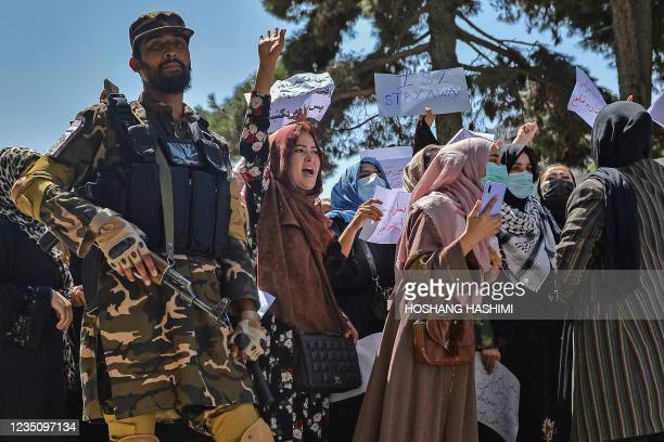 Taliban fighter stands guard as Afghan women shout slogans during an anti-Pakistan protest rally, near the Pakistan embassy in Kabul on September 7,...