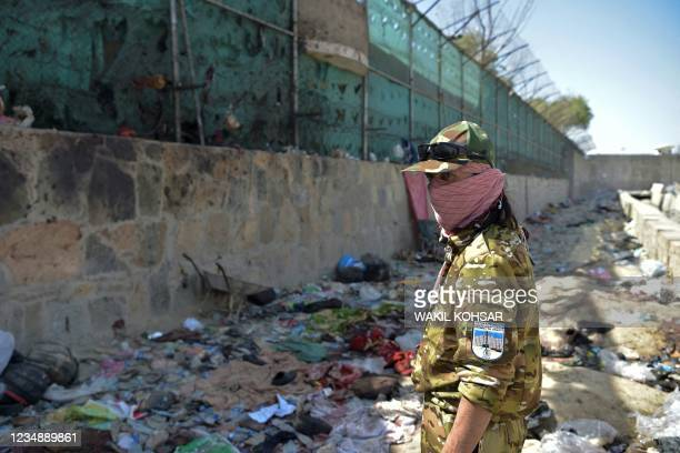Taliban fighter stands guard at the site of the August 26 twin suicide bombs, which killed scores of people including 13 US troops, at Kabul airport...