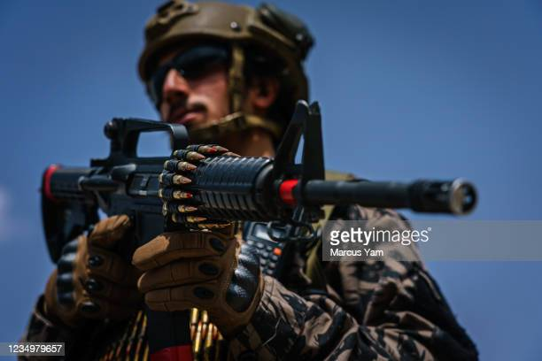 Taliban fighter stands ready with his rifle in as the militant group secure the Hamid Karzai International Airport, in the wake of the American...