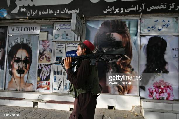 Taliban fighter walks past a beauty salon with images of women defaced using spray paint in Shar-e-Naw in Kabul on August 18, 2021.
