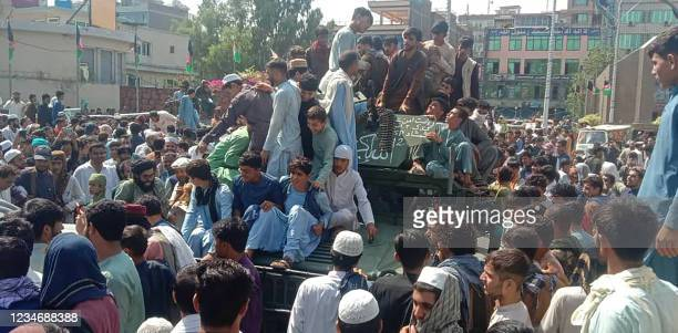 Taliban fighters and local people sit on an Afghan National Army Humvee vehicle on a street in Jalalabad province on August 15, 2021.