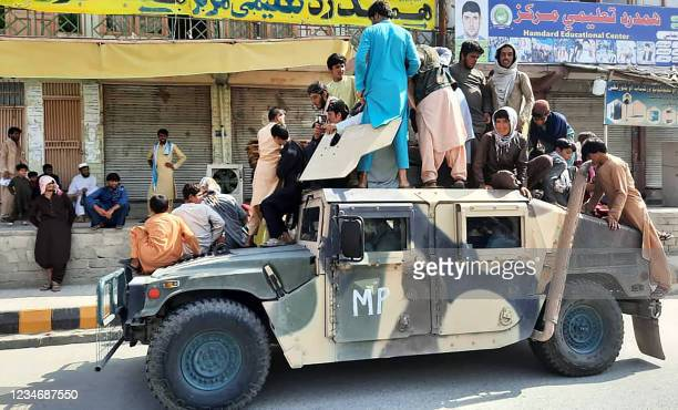 Taliban fighters and local residents sit on an Afghan National Army Humvee vehicle along the roadside in Laghman province on August 15, 2021.
