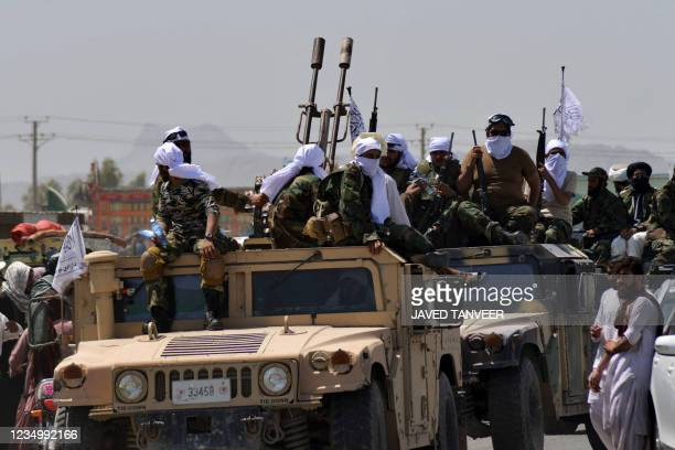 Taliban fighters atop Humvee vehicles parade along a road to celebrate after the US pulled all its troops out of Afghanistan, in Kandahar on...