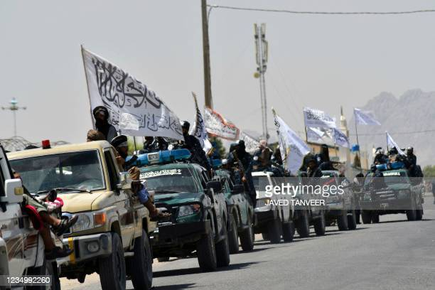 Taliban fighters atop vehicles with Taliban flags parade along a road to celebrate after the US pulled all its troops out of Afghanistan, in Kandahar...