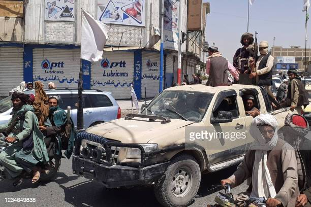 Taliban fighters drive an Afghan National Army vehicle through a street in Kandahar on August 13, 2021.