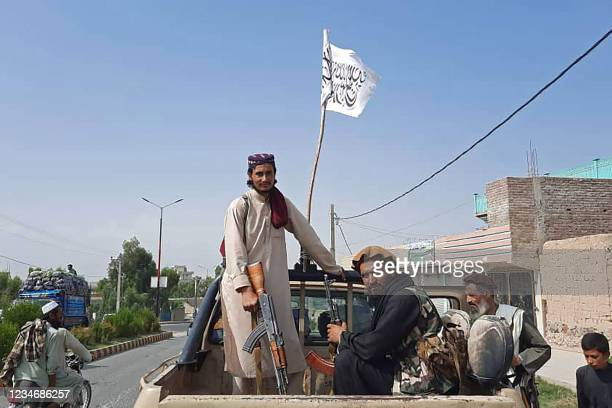 Taliban fighters drive an Afghan National Army vehicle through the streets of Laghman province on August 15, 2021.