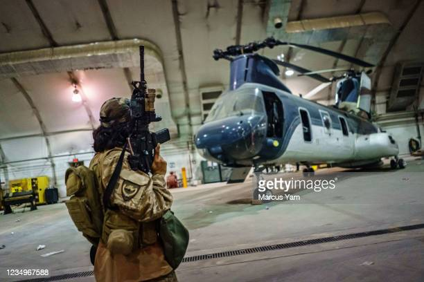 Taliban fighters from the Fateh Zwak unit, wielding American supplied weapons, equipment and uniforms, storm into the Kabul International Airport to...