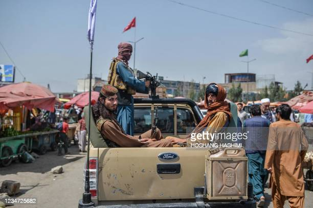 Taliban fighters on a pick-up truck move around a market area, flocked with local Afghan people at the Kote Sangi area of Kabul on August 17 after...