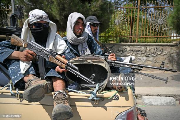 Taliban fighters patrol a street in Kabul on August 29 as suicide bomb threats hung over the final phase of the US military's airlift operation from...