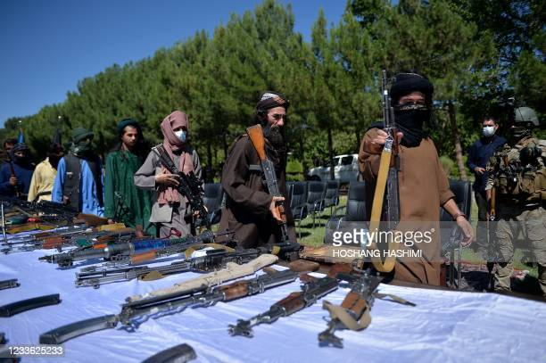 Taliban fighters put down their weapons as they surrendered to join the Afghanistan government during a ceremony in Herat on 24, 2021.
