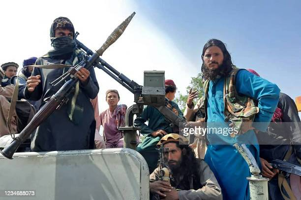 Taliban fighters sit over a vehicle on a street in Laghman province on August 15, 2021.