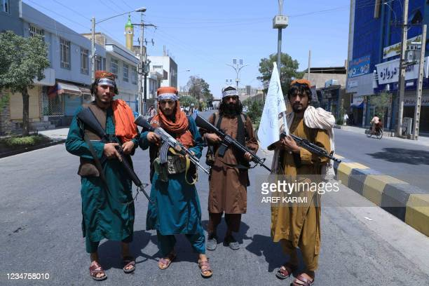 Taliban fighters stand guard along a road near the site of an Ashura procession which is held to mark the death of Imam Hussein, the grandson of...