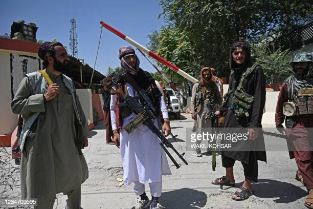 Taliban fighters stand guard along a roadside near the Zanbaq Square in Kabul on August 16, 2021 as the Taliban were in control of Afghanistan after...