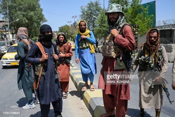 Taliban fighters stand guard along a street near the Zanbaq Square in Kabul on August 16 after a stunningly swift end to Afghanistan's 20-year war,...