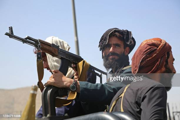 Taliban fighters stand guard in a vehicle along the roadside in Kabul on August 16 after a stunningly swift end to Afghanistan's 20-year war, as...